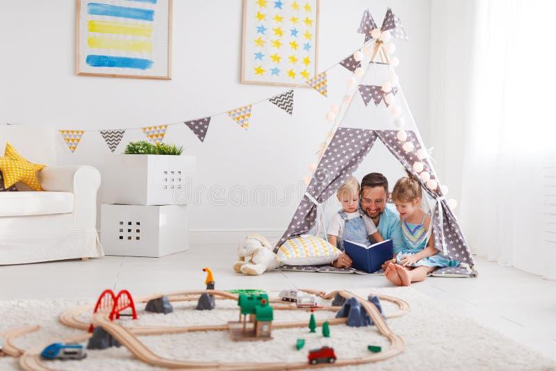 Familievader die aan kinderenboek thuis lezen in tent stock afbeeldingen