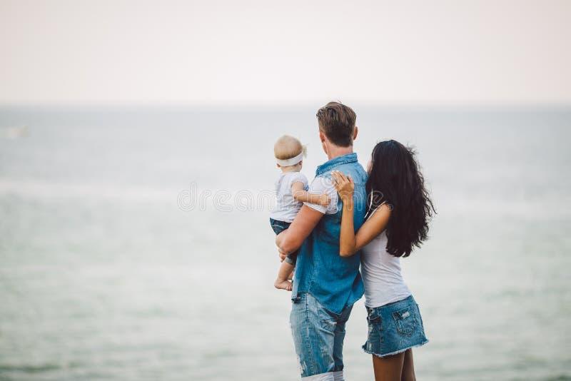 Familievakantie in aard Drie, Mamma, Papa, dochter één jaar die zich met ruggen die op klip bevinden overzees overzien E stock afbeeldingen