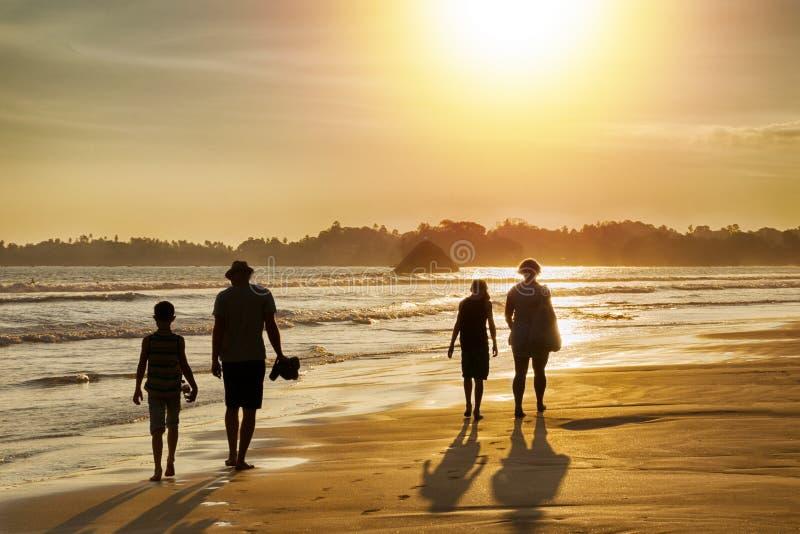 Familievakantie in de keerkringen door het overzees - silhouetten van mensen die op het strand bij zonsondergang lopen stock fotografie