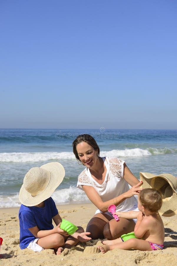 Familievakantie op strand: Moeder en jonge geitjes royalty-vrije stock foto's