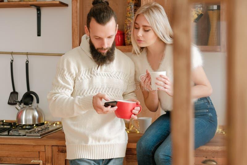 Familievrijetijd-paar koffiekeuken-smartphone stock fotografie