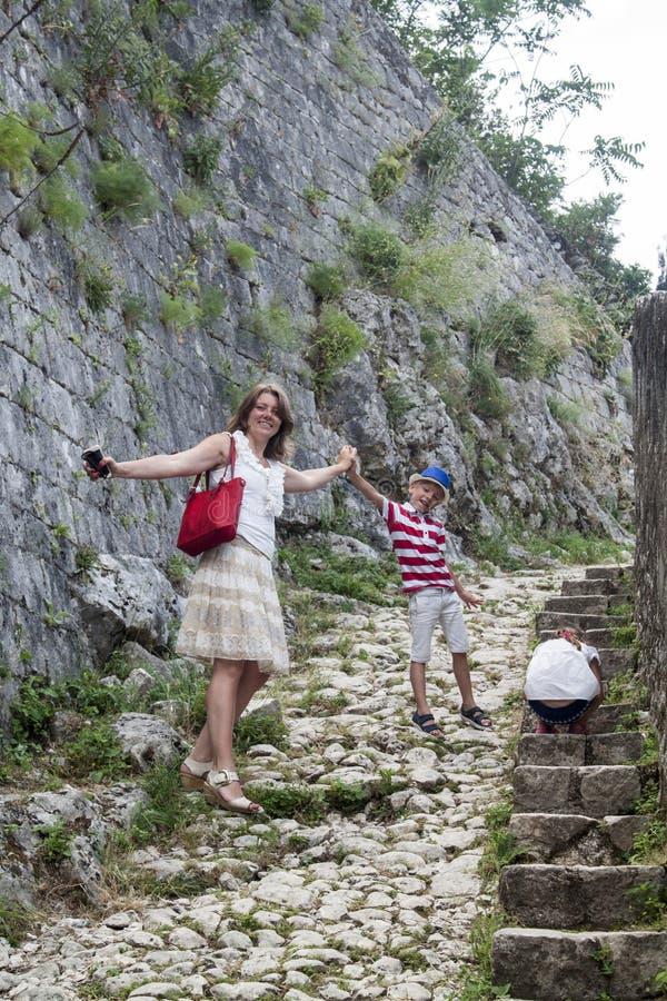 Familiewaarde de gelukkige moeder met haar zoon en dochter beklimt omhoog de berg de stappen om te zien het overweldigen vanaf de royalty-vrije stock foto's