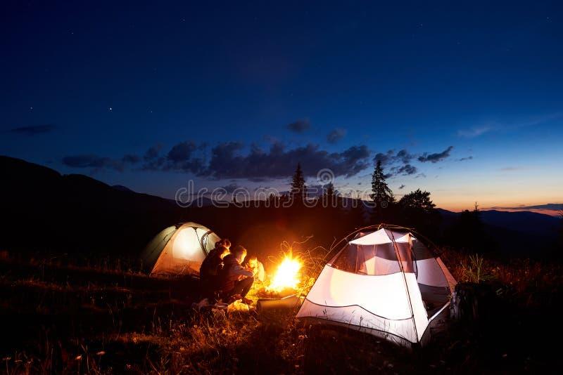 Familiewandelaars die een rust hebben bij nacht die in bergen kamperen royalty-vrije stock fotografie