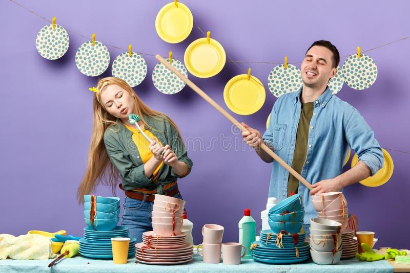 Familiewas, schoonmakende keuken met pret stock afbeeldingen
