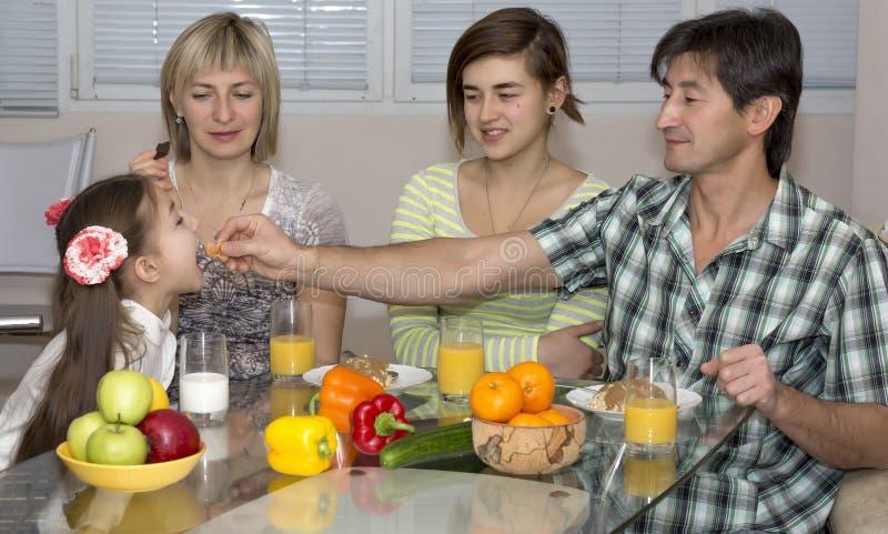Familiezitting bij Lijst die Maaltijd samen eten royalty-vrije stock afbeeldingen