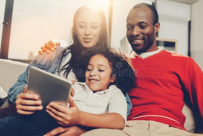 Familiezitting binnen en genietend van moderne technologie royalty-vrije stock afbeelding