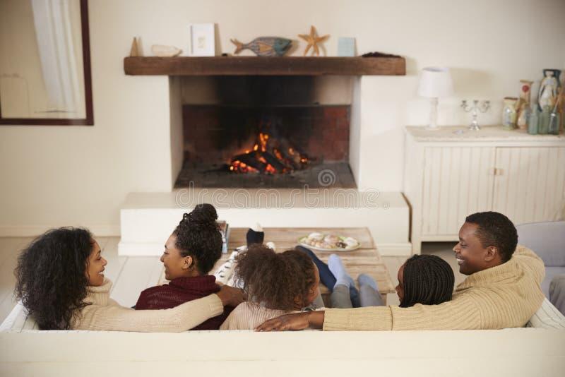 Familiezitting op de Open Brand van Sofa In Lounge Next To royalty-vrije stock afbeelding