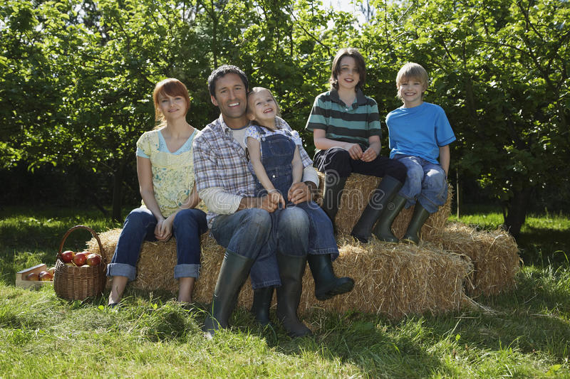 Familiezitting op Hay Bales Near Orchard royalty-vrije stock fotografie