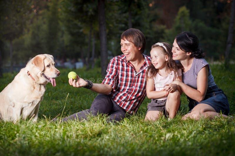 Familiezitting op het gras met hond royalty-vrije stock foto