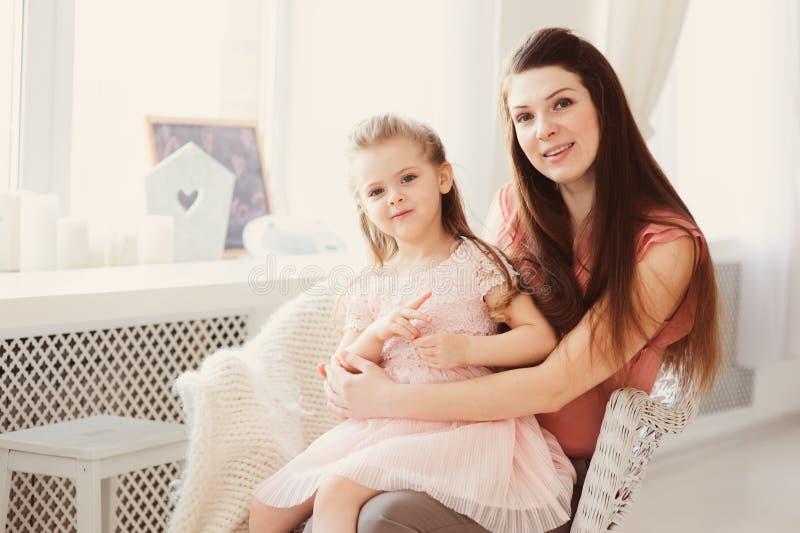 Familiezitting op stoel thuis Toevallige levensstijlvangst van moeder en peuterdochter stock afbeeldingen