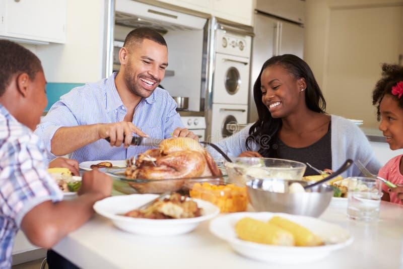 Familiezitting rond Lijst die thuis Maaltijd eten stock foto
