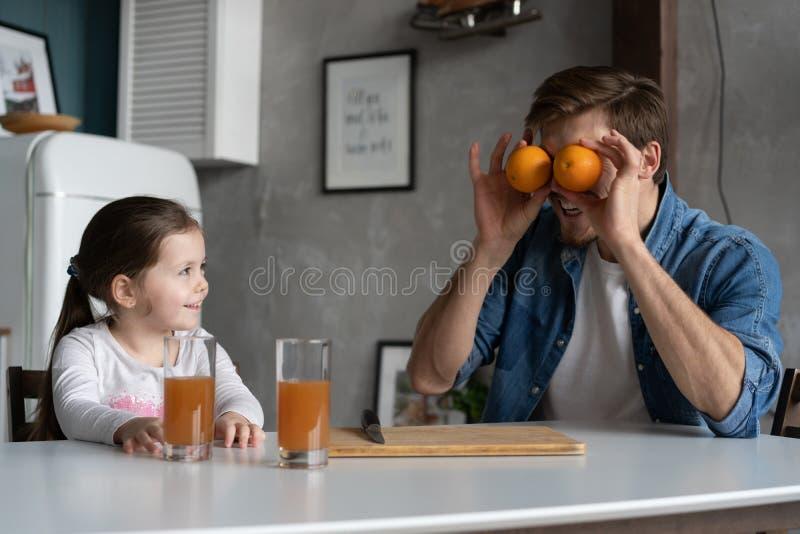 Familj, äta och folkbegrepp - lycklig fader och dotter som har frukosten hemma arkivbild