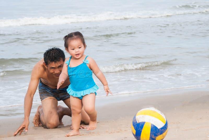familj Asiatet behandla som ett barn flickan och fadern som spelar fotboll på stranden arkivbild
