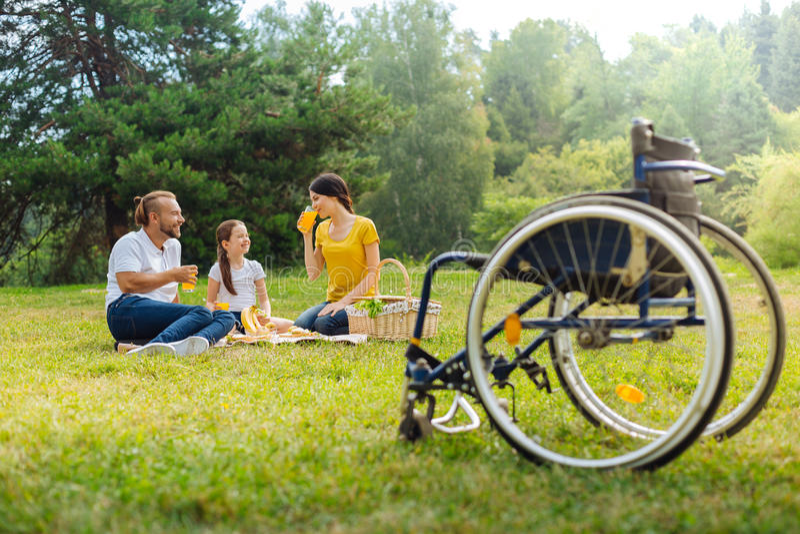 Familj av en handikappade personerman som dricker fruktsaft i ängen royaltyfri bild