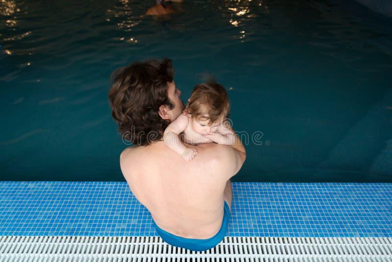 Familj av fadern och hans lilla dottersammanträde på kanten av simbassängen Barnet avlar, och hans lilla gulliga nyfött behandla  arkivfoton