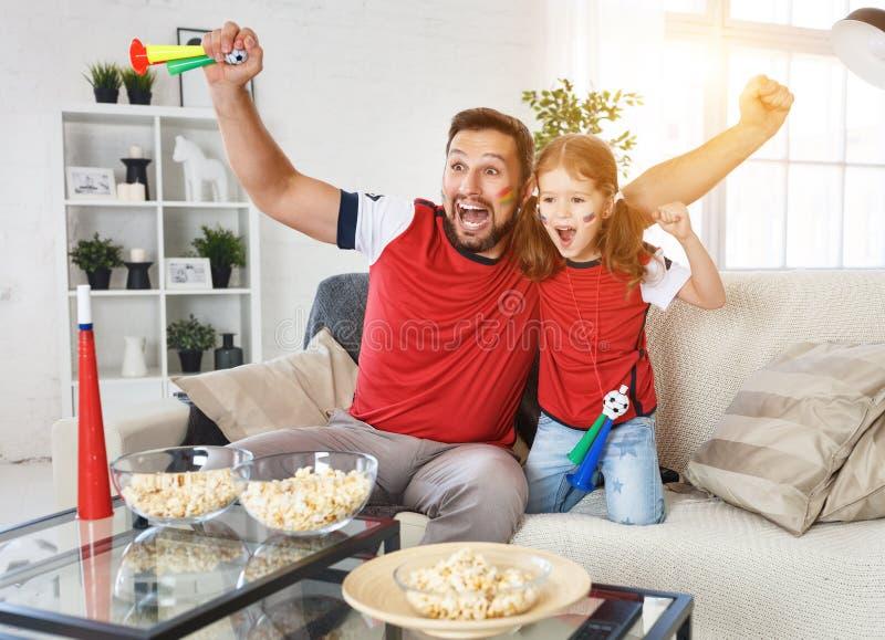 Familj av fans som hemma håller ögonen på en fotbollsmatch på TV arkivfoto