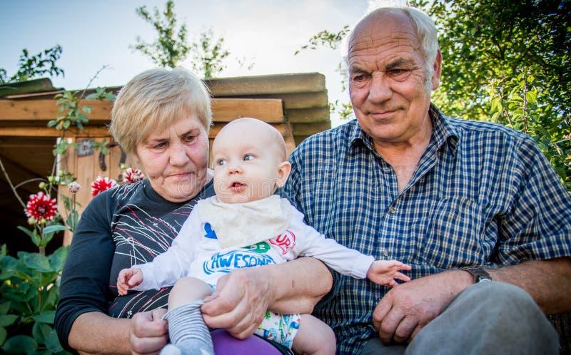 Familj av farmodern, farfadern och sonsonen arkivfoton