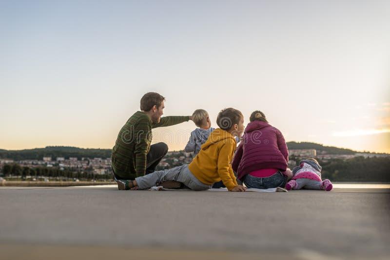 Familj av fem som sitter på träpir royaltyfria bilder