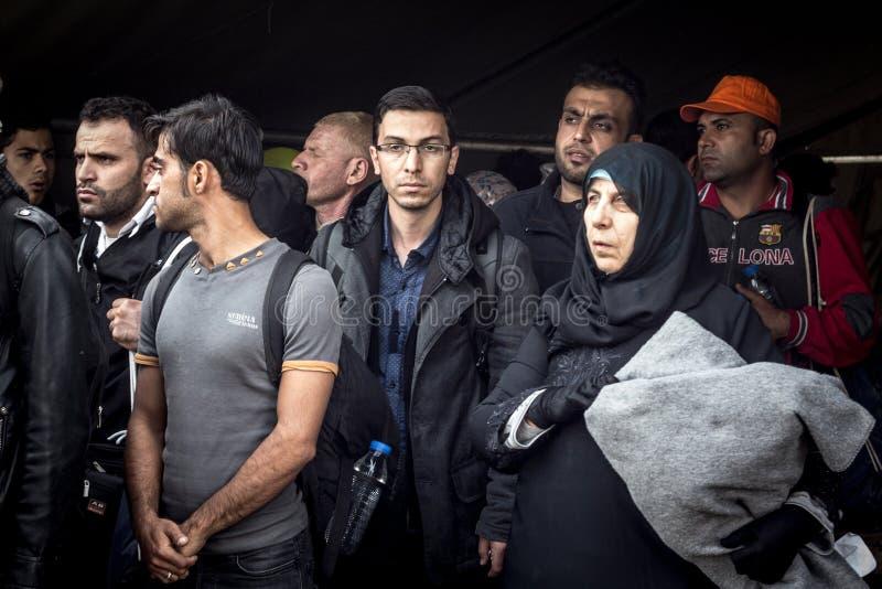Familj av flyktingar, män och kvinnor som bär islamiska halsdukar och att rymma deras barn som väntar för att korsa den KroatienS fotografering för bildbyråer