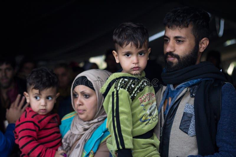 Familj av flyktingen, mannen och kvinnan och att rymma deras barn som väntar för att korsa den KroatienSerbien gränsen, på den Ba royaltyfria foton