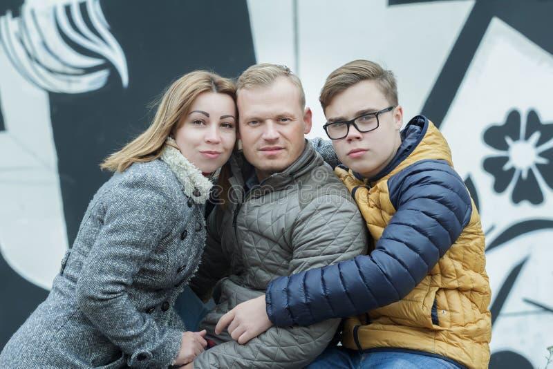 Familj av fridfullt omfamna folk på svartvit väggbakgrund arkivfoton