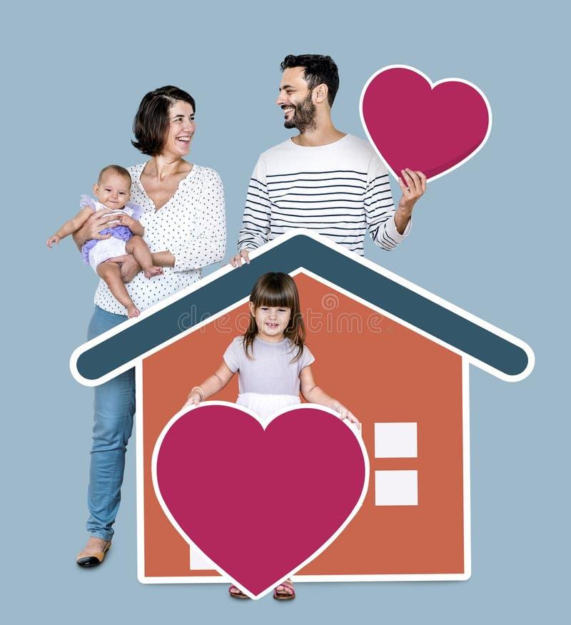 Familj av fyra i ett älska hem arkivfoton