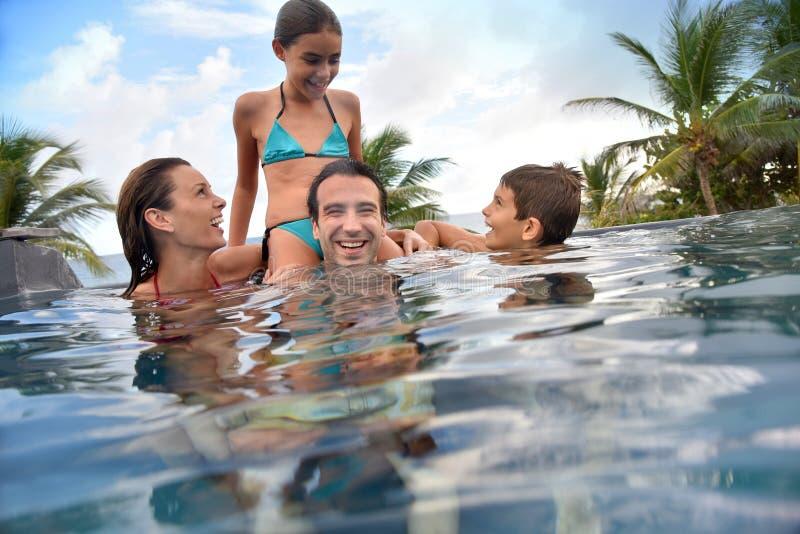 Familj av fyra i simbassängen som har gyckel arkivbild