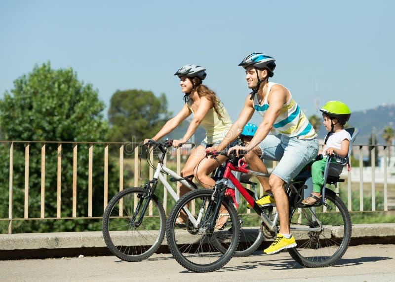 Familj av fyra med cyklar arkivbild