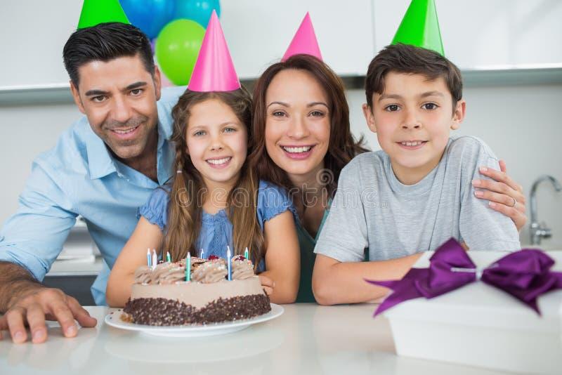 Familj av fyra med kakan och gåvor på födelsedagpartiet arkivbilder