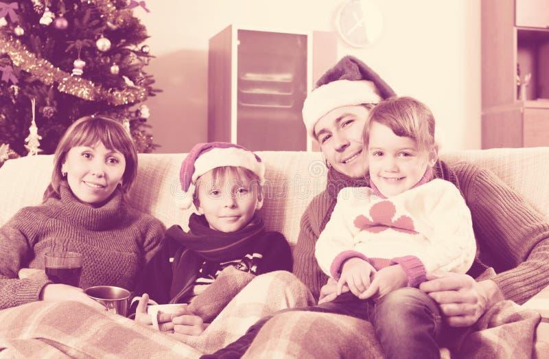 Familj av fyra på soffan hemma arkivfoton