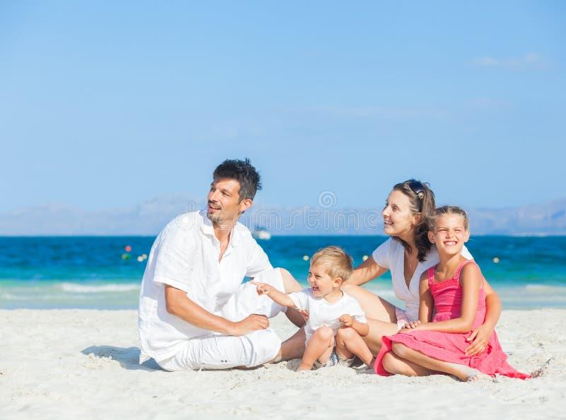 Familj av fyra på tropisk strand arkivfoto