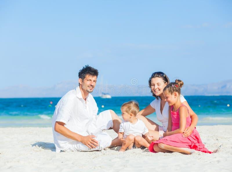 Familj av fyra på tropisk strand fotografering för bildbyråer