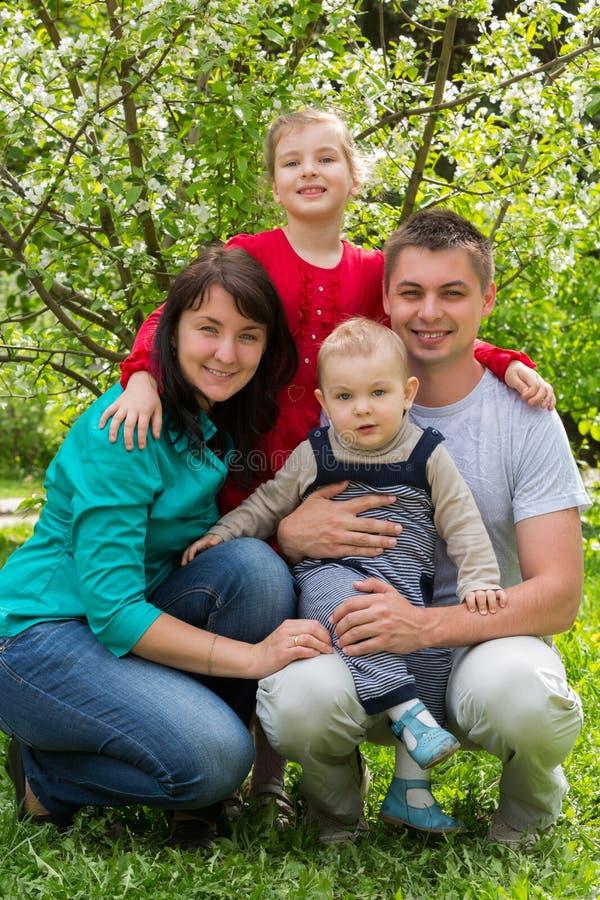 Familj av fyra som går i parkera. royaltyfri fotografi