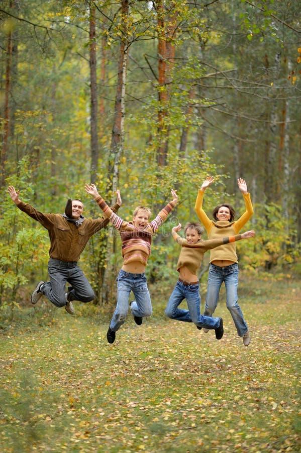 Familj av fyra som har gyckel i skog arkivbild