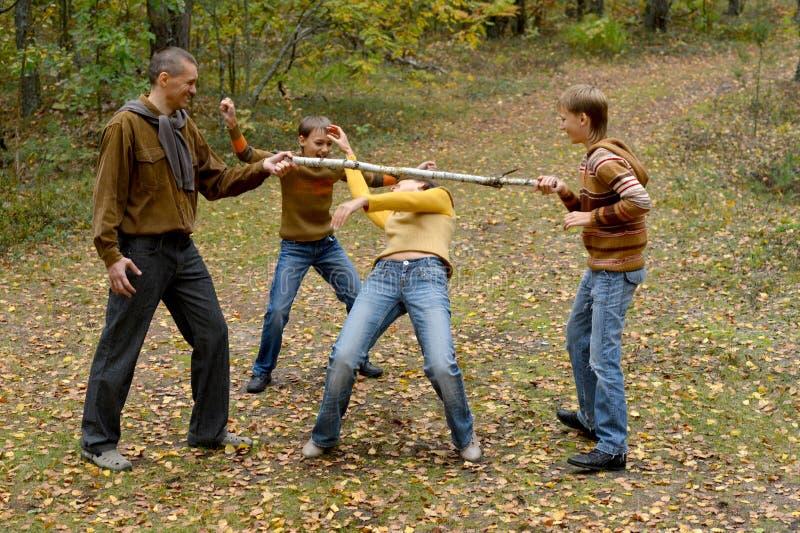 Familj av fyra som har gyckel i skog arkivfoto