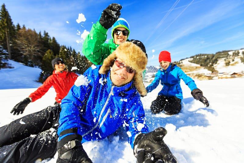 Familj av fyra som har gyckel i snön royaltyfri foto