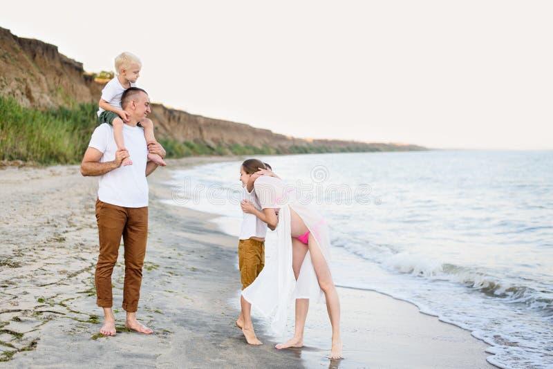 Familj av fyra som har gyckel på kusten f?r?ldrar och tv? s?ner Lycklig v?nlig familj royaltyfri foto