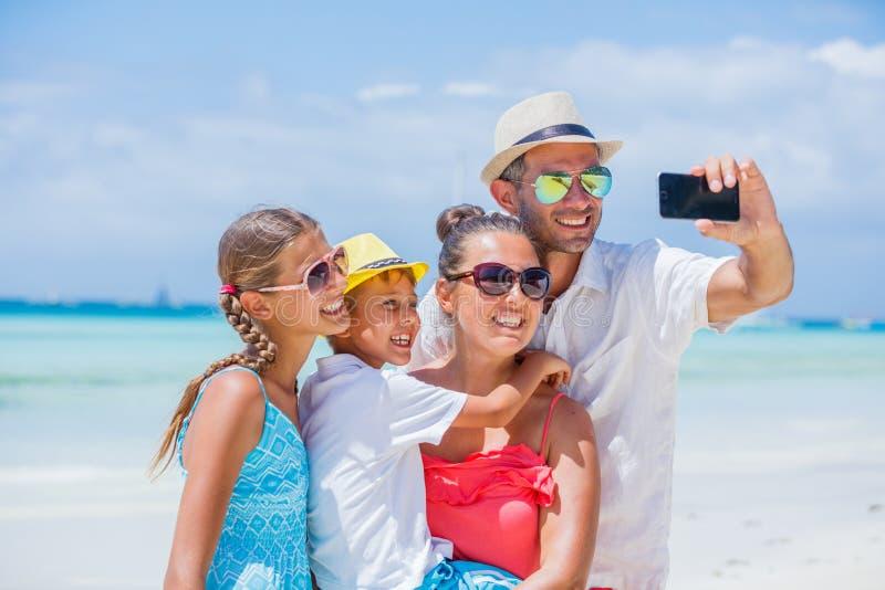 Familj av fyra som har gyckel på stranden fotografering för bildbyråer