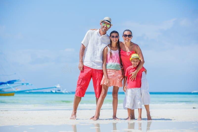 Familj av fyra som har gyckel på stranden arkivfoton
