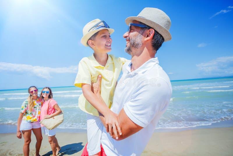 Familj av fyra som har gyckel på stranden royaltyfria bilder