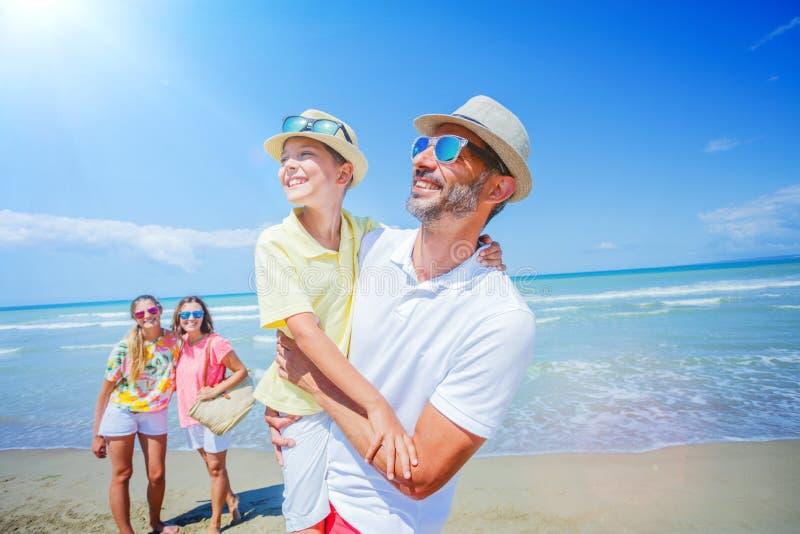 Familj av fyra som har gyckel på stranden royaltyfria foton