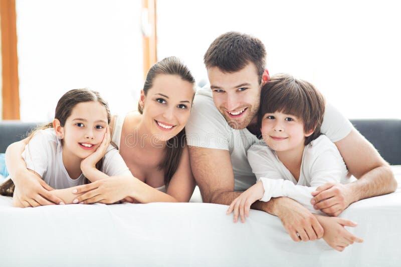 Familj av fyra som ligger på säng arkivfoton