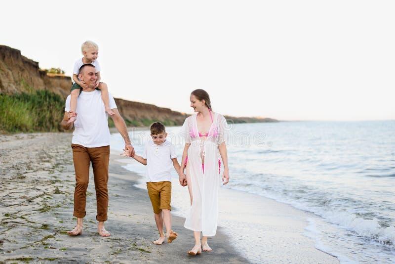 Familj av fyra som promenerar kusten f?r?ldrar och tv? s?ner Lycklig v?nlig familj royaltyfria bilder