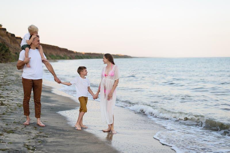 Familj av fyra som promenerar kusten f?r?ldrar och tv? s?ner Lycklig v?nlig familj arkivfoton
