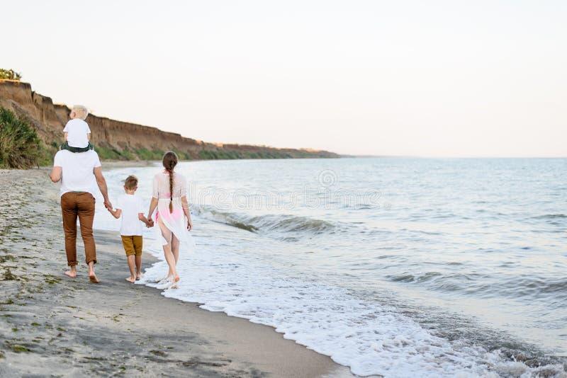 Familj av fyra som promenerar kusten f?r?ldrar och tv? s?ner tillbaka sikt arkivbilder
