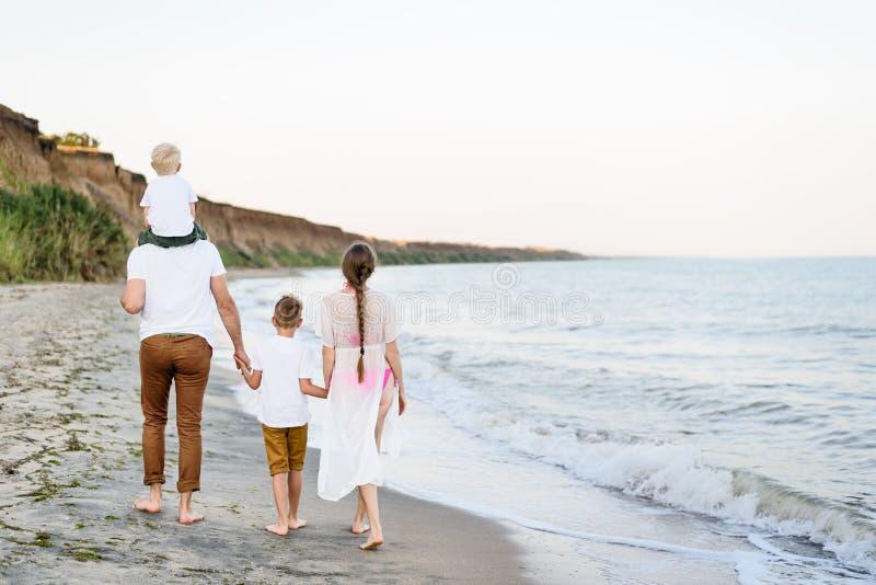 Familj av fyra som promenerar kusten f?r?ldrar och tv? s?ner tillbaka sikt royaltyfri bild