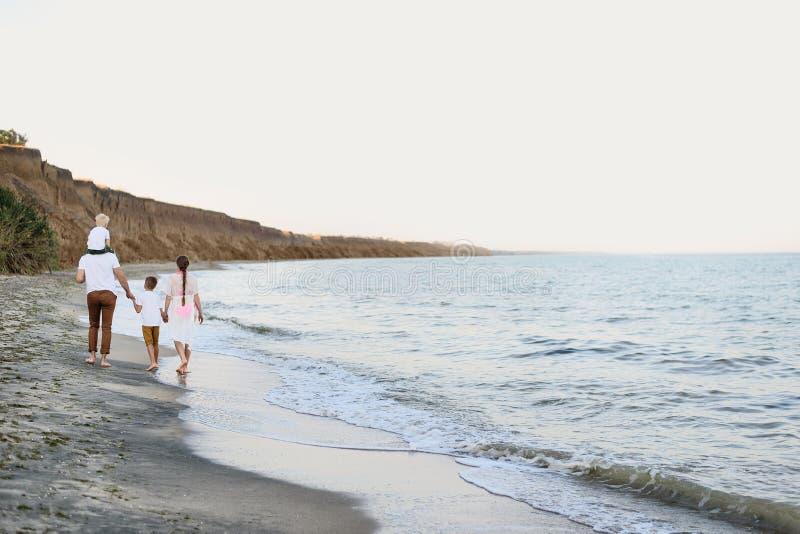 Familj av fyra som promenerar kusten f?r?ldrar och tv? s?ner tillbaka sikt fotografering för bildbyråer