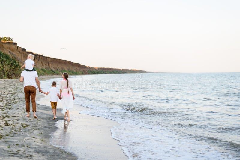 Familj av fyra som promenerar kusten f?r?ldrar och tv? s?ner tillbaka sikt royaltyfri foto