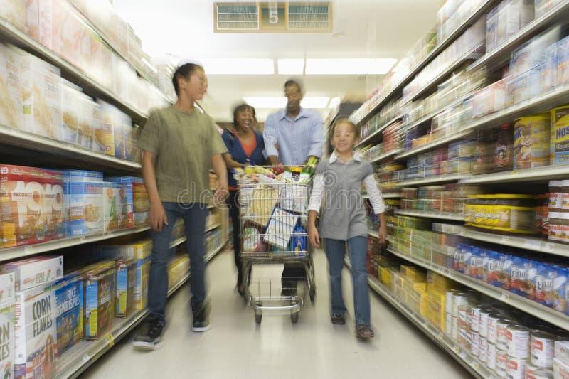 Familj av fyra som shoppar i supermarket fotografering för bildbyråer