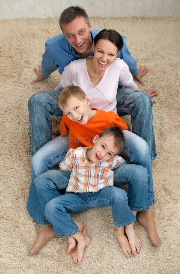 Familj av fyra som sitter på mattan arkivfoto